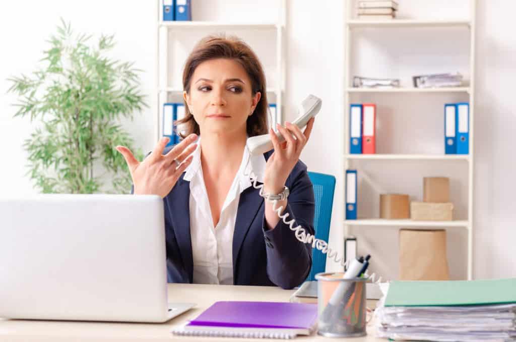 Eine Frau sitzt an einem Schreibtisch und hält skeptisch einen Telefonhörer in der Hand (Boreout).