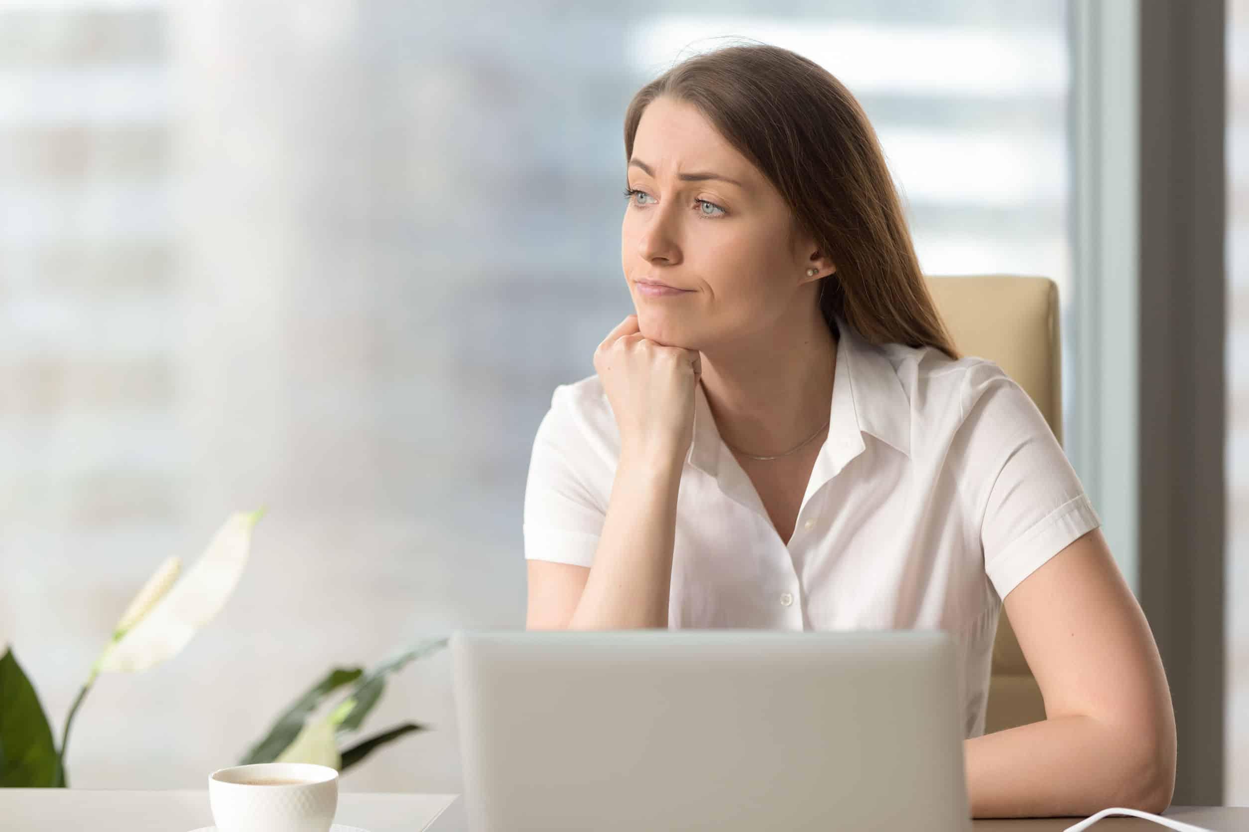 Boreout: eine Frau sitzt nachdenklich vor einem Laptop, stützt ihr Kinn mit der einen Hand und schaut zur Seite.