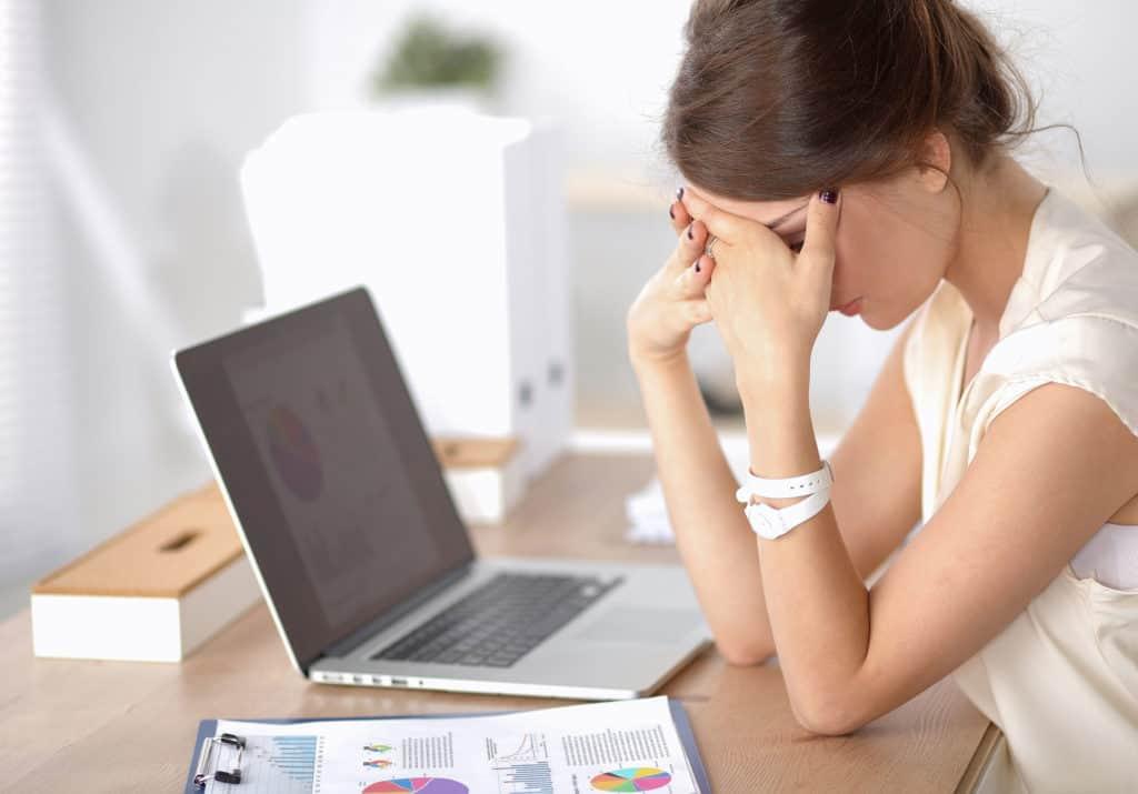 Boreout: eine Frau sitzt vor einem Laptop und hält sich mit ihren Händen die Augen zu.
