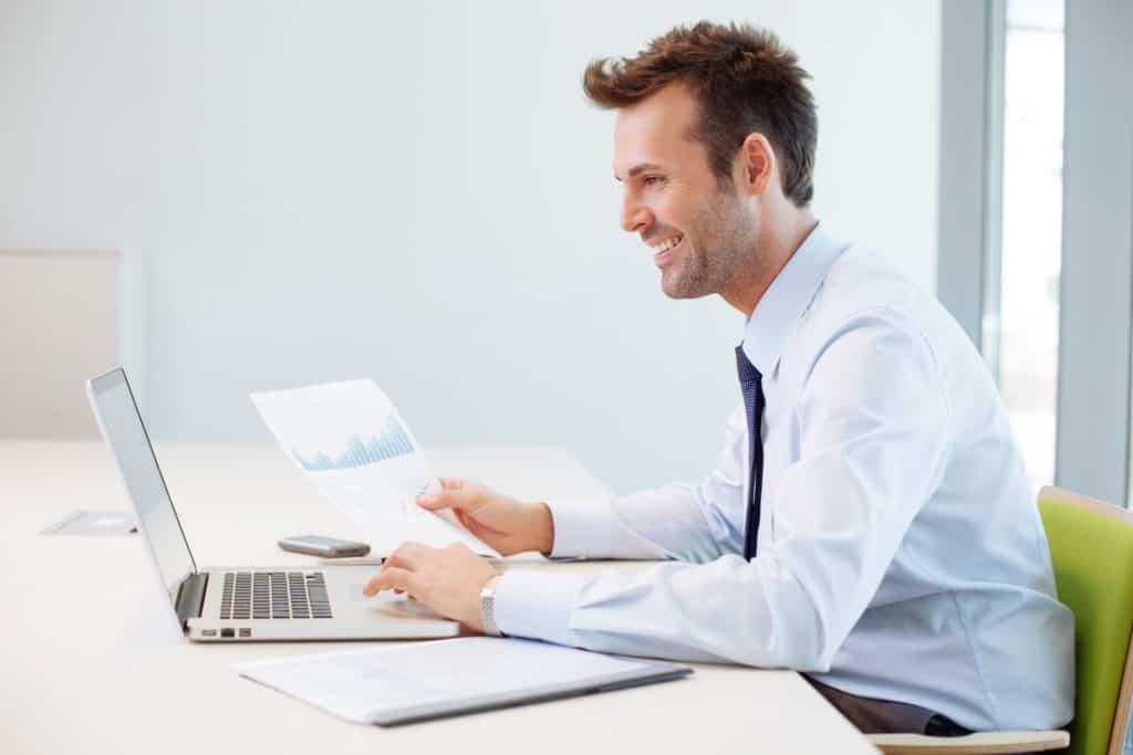 Ein Arbeitnehmer arbeitet lächelnd an einem Laptop (Boreout).