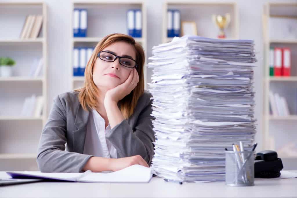 Boreout: eine Frau sitzt an einem Schreibtisch, der mit Unterlagen überfüllt ist und stützt ihren Kopf mit der einen Hand ab.
