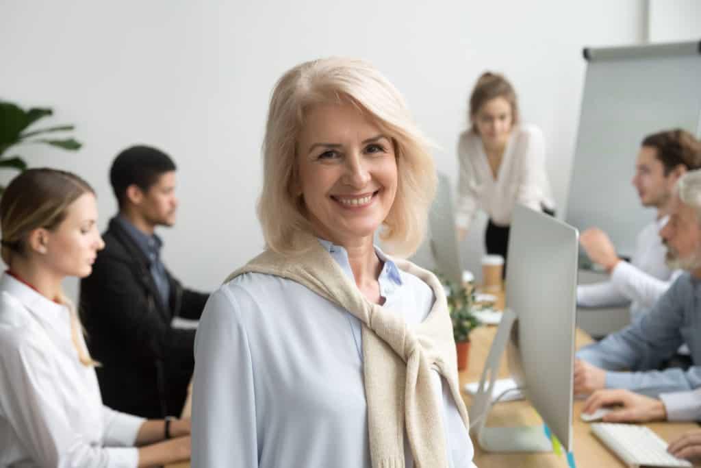 Midlife Crisis Frauen: Middle Ager Frau steht lächelnd vor einem Team.