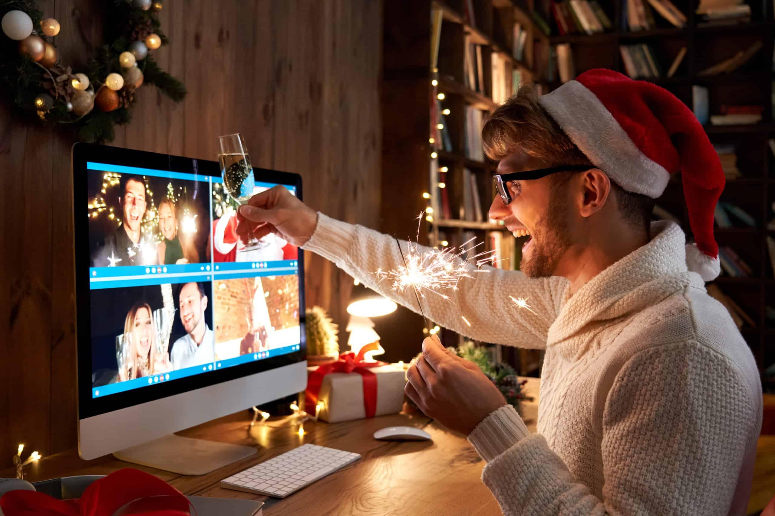 Virtuelle Weihnachtsfeier: ein lachender Mann trägt eine rote Weihnachtsmütze, hält eine gezündete Wunderkerze und ein gefülltes Sektglas in den Händen und stoßt mit seinen Kollegen in einem Video-Call an.