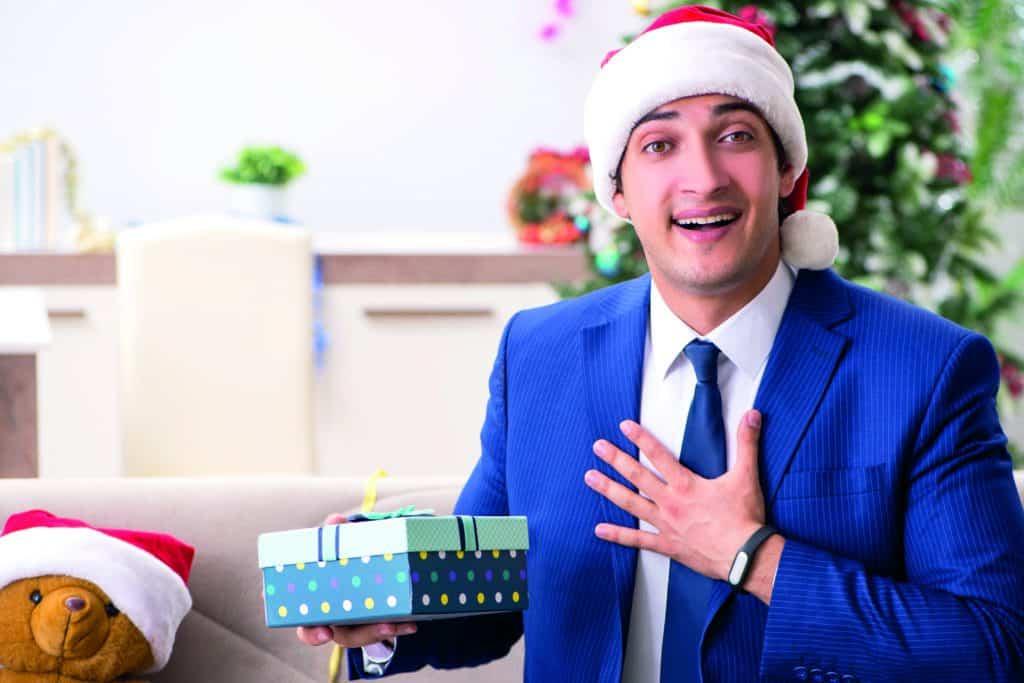 Virtuelle Weihnachtsfeier: ein Mitarbeiter freut sich über eine weihnachtliche Geschenkbox