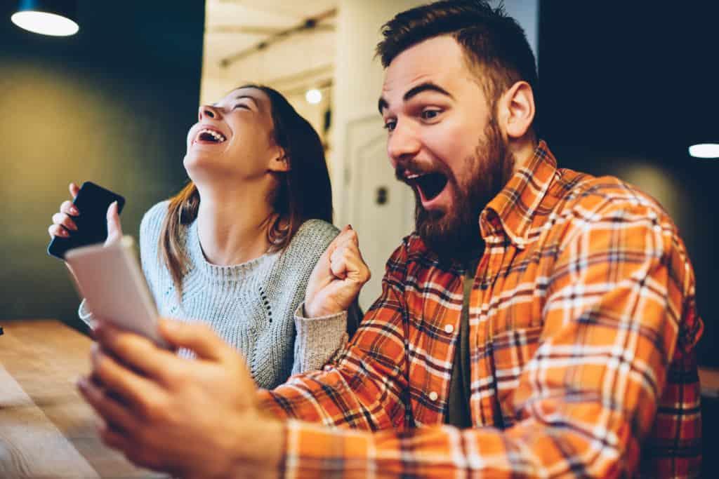 Virtuelle Weihnachtsfeier: ein Mann und eine Frau schauen auf ein Tablet und freuen sich.