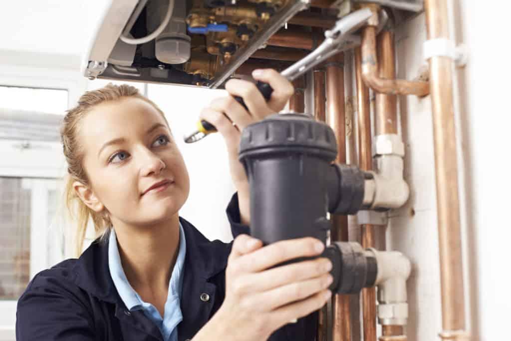 Neues Gebäudeenergiegesetz: eine Frau repariert Heizungsrohre