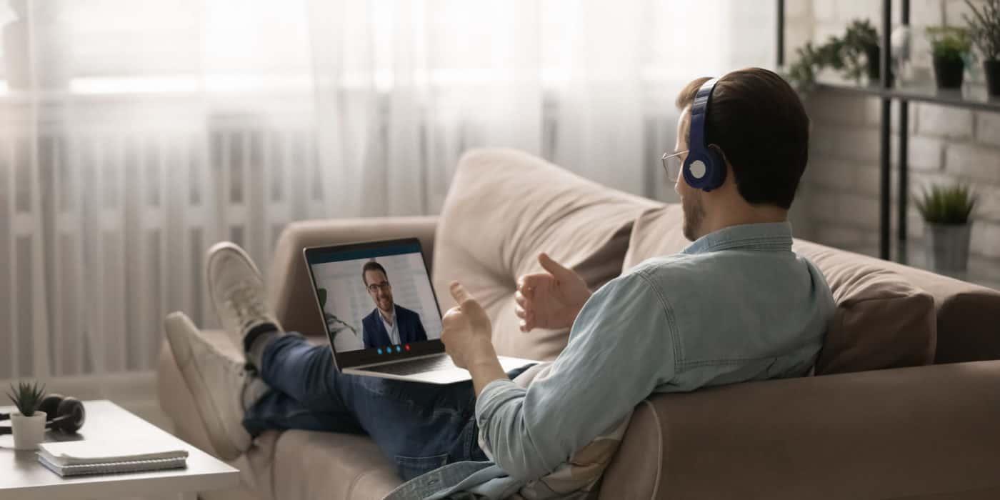 Ein junger Mann führt ein Bewerbungsgespräch vom Sofa aus.
