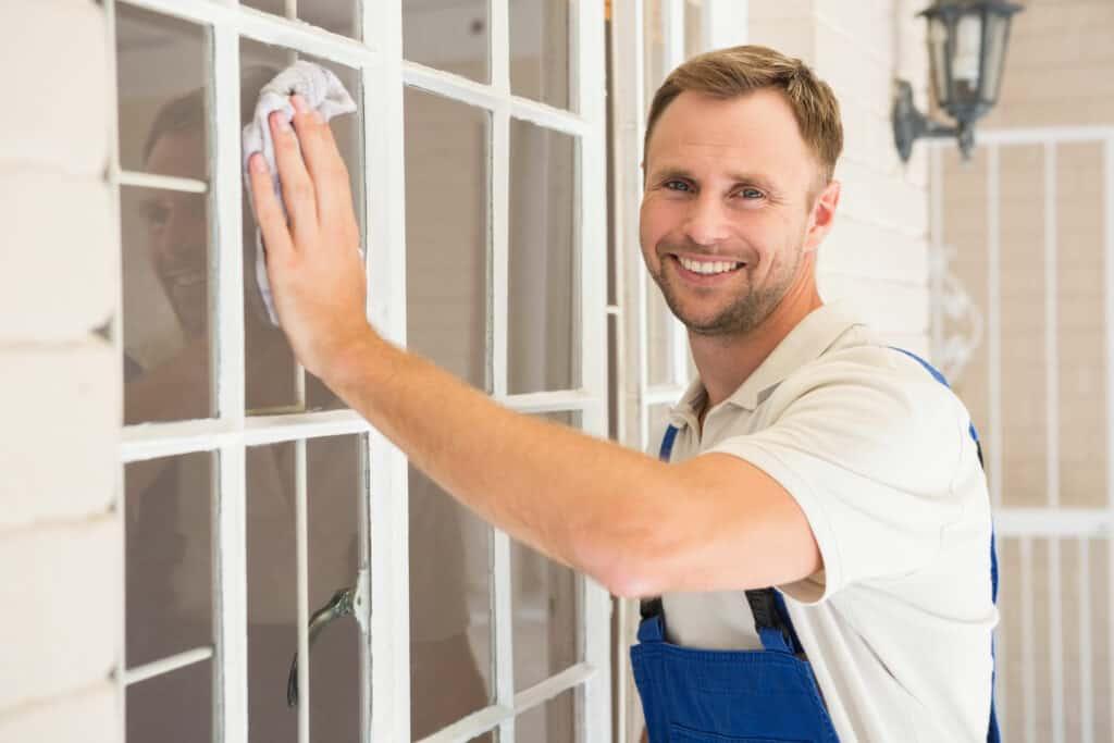Kunststofffenster reinigen: Mann putzt Fenster