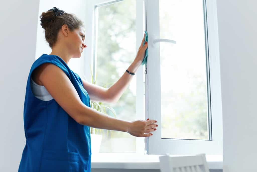 Kunststofffenster reinigen: Frau putzt Fenster
