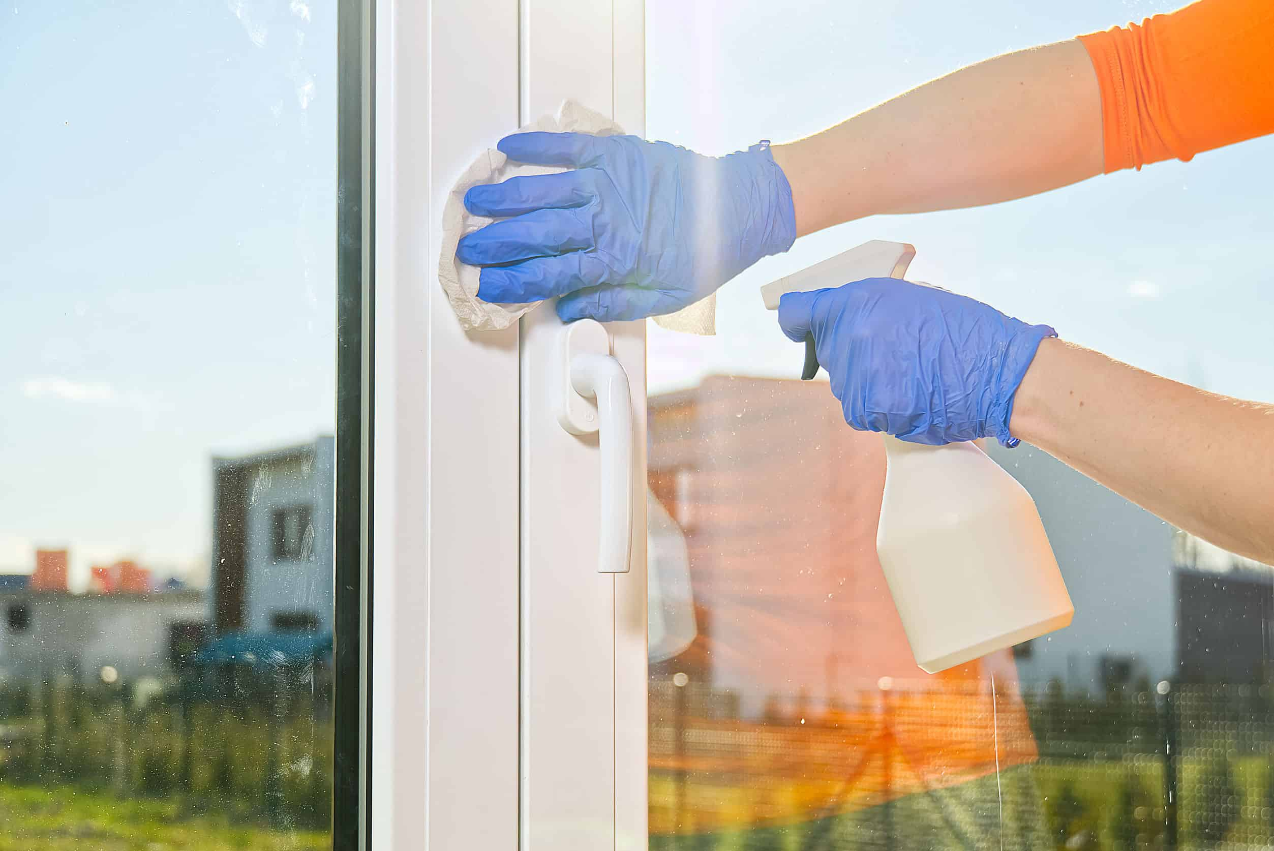 Kunststofffenster reinigen: Kunststofffenster, Hände mit Gummihandschuhen