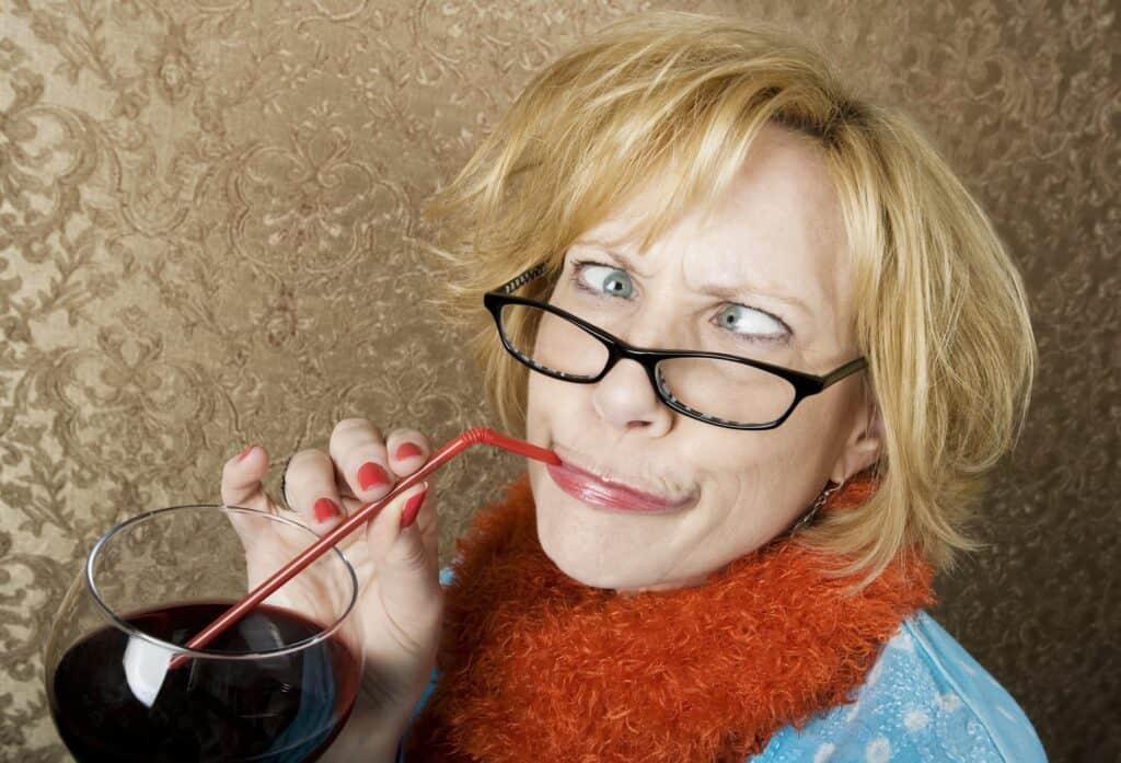 Stellensuche mit Social Media: eine Frau trinkt aus einem Strohhalm ein großes Glas Rotwein und schaut dabei komisch in die Kamera.