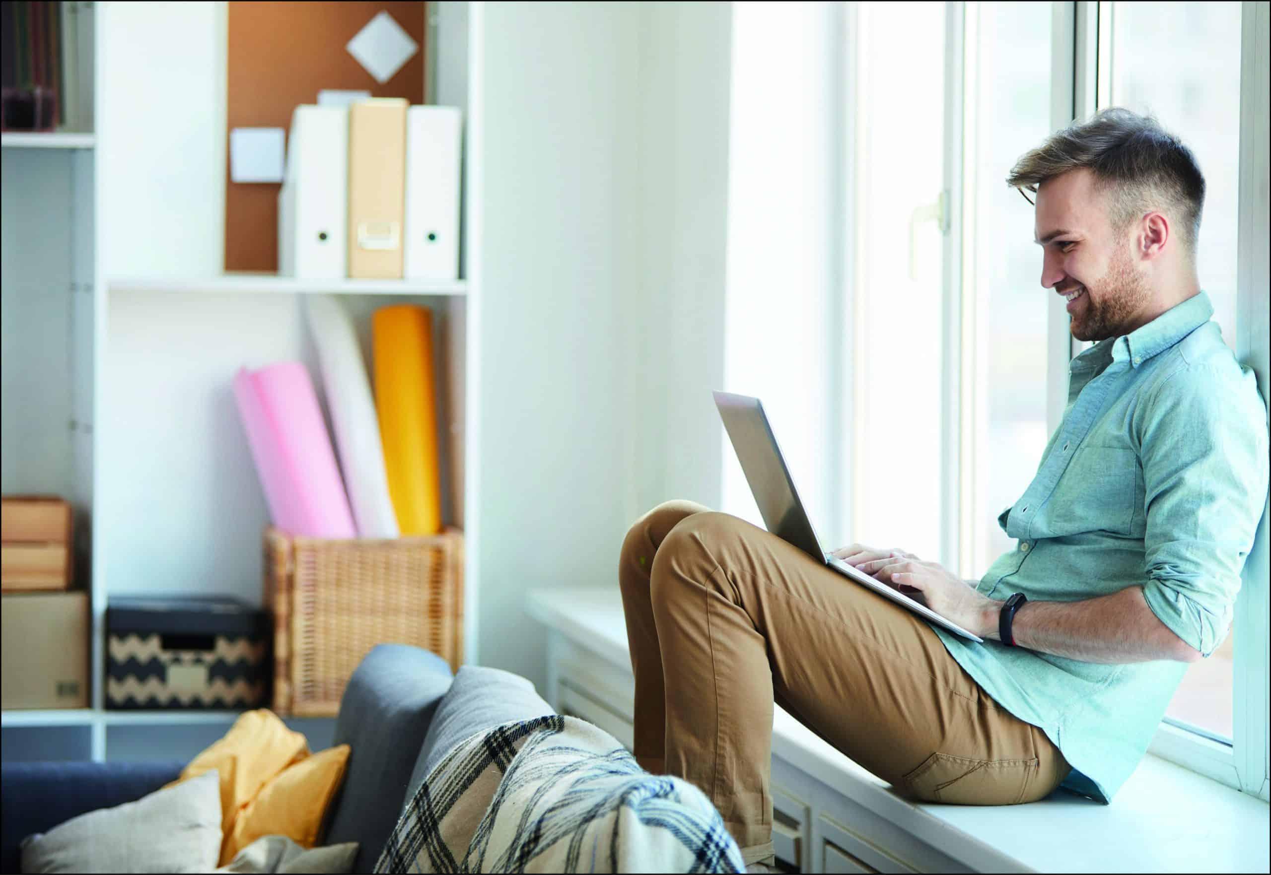 Stellensuche mit Social Media: ein Mann sitzt lachend vor einem Laptop