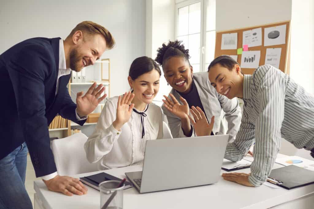 Ein Team aus internationalen Mitarbeiten fröhrlich vor dem Laptop. (Fremdsprachen)