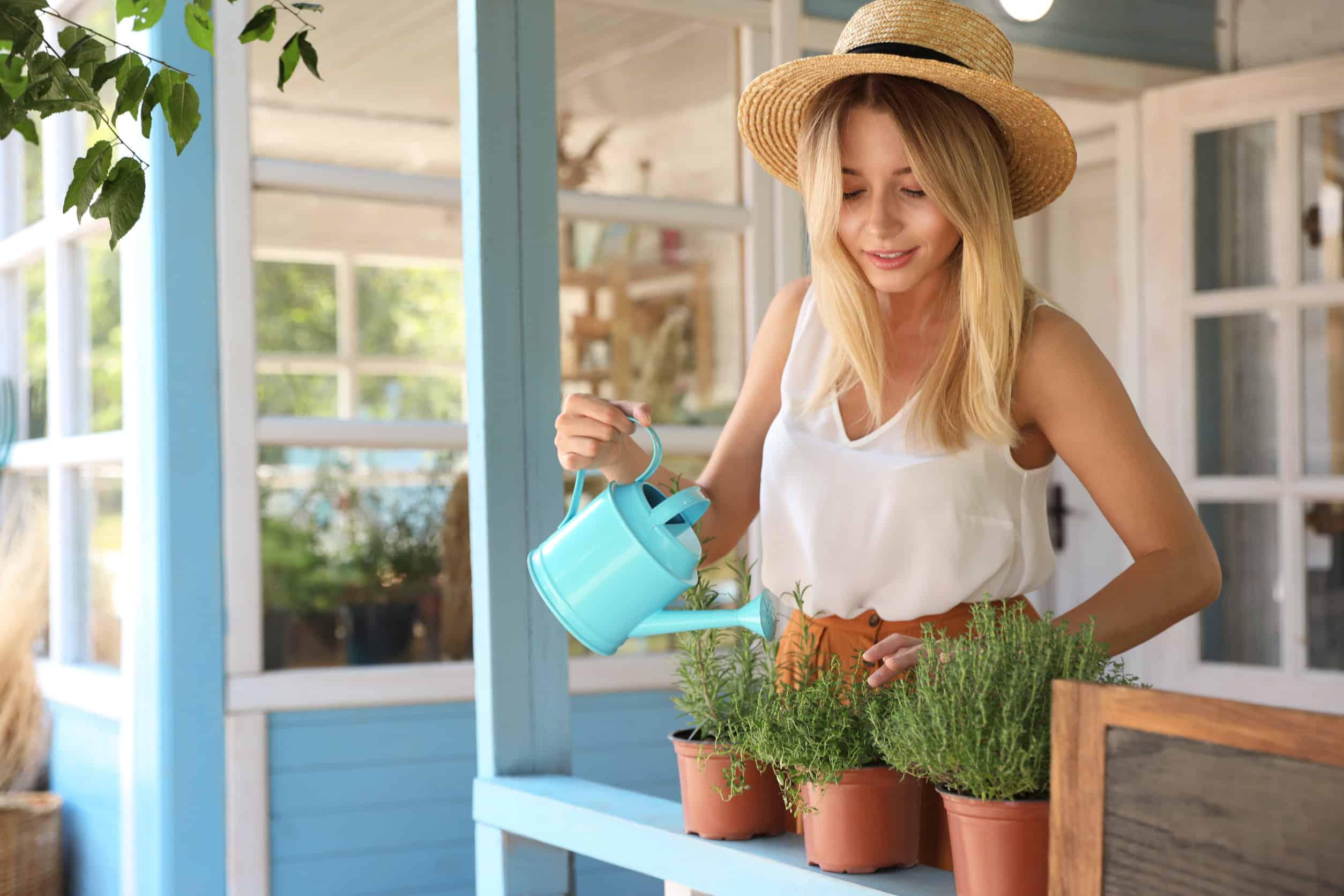Junge Frau beim Blumen gießen im Tiny House