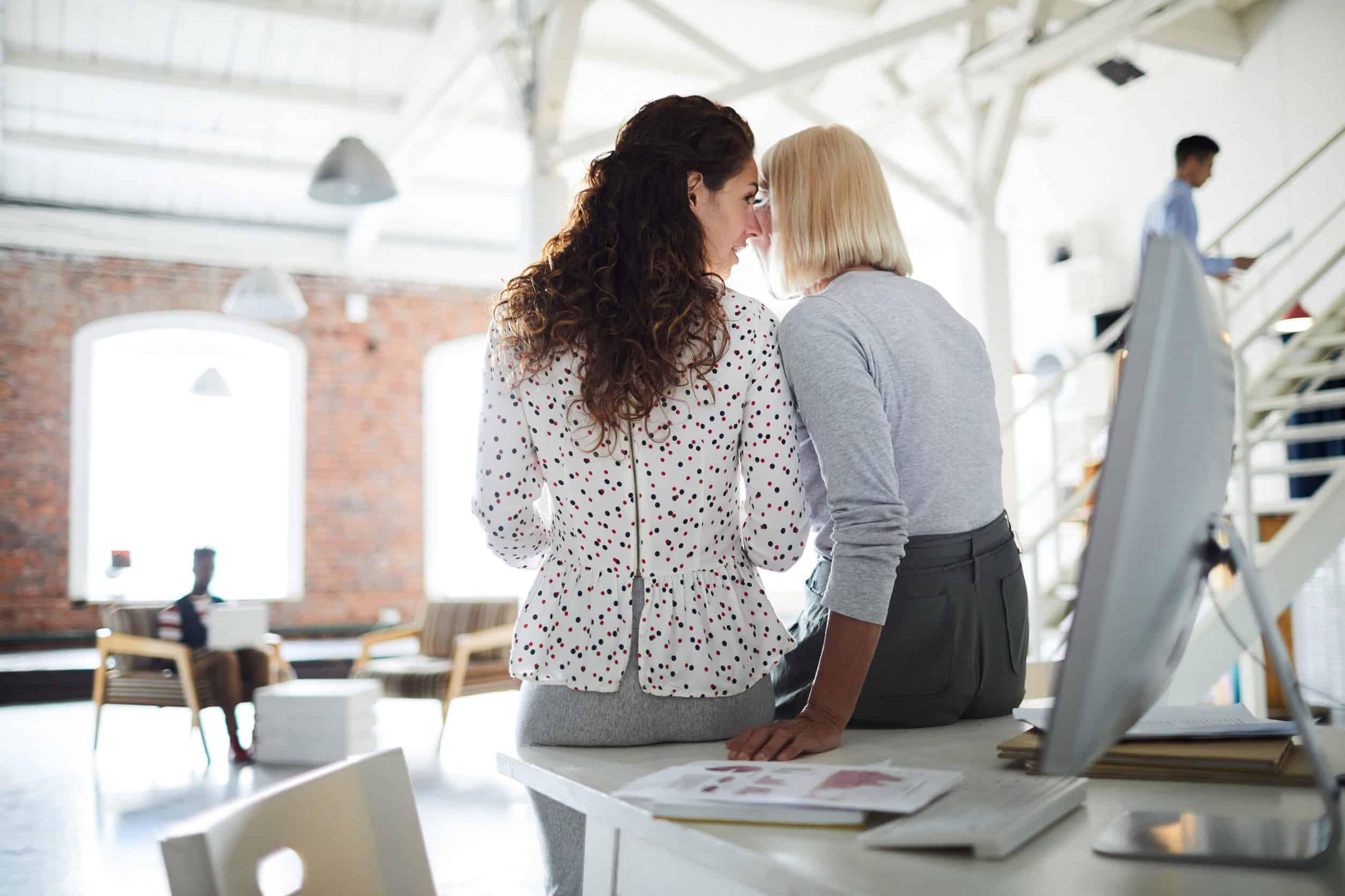 Klatsch und Tratsch am Arbeitsplatz: Zwei Frauen flüstern ins Ohr.