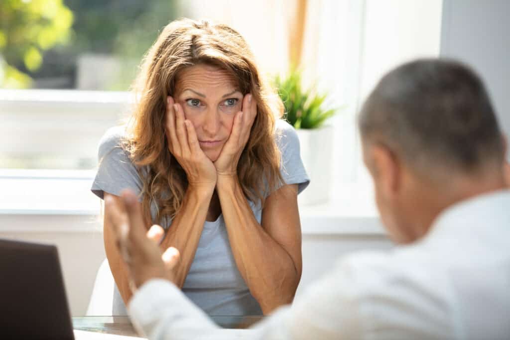 Klatsch und Tratsch am Arbeitsplatz: Sorgenvolle Frau im Gespräch mit einem Mann.