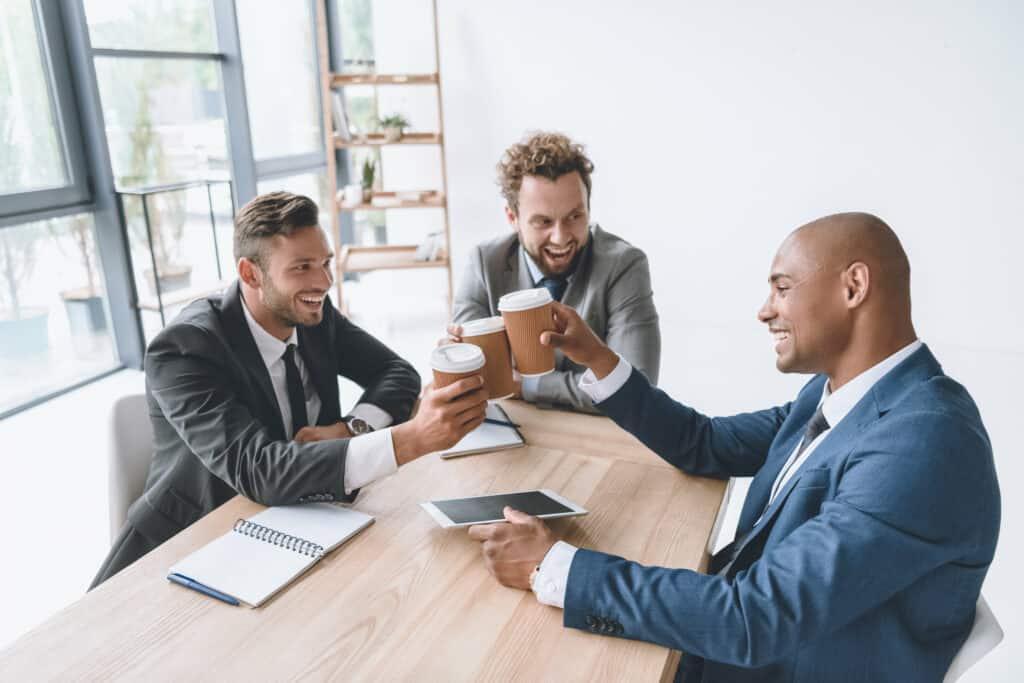 Klatsch und Tratsch am Arbeitsplatz: drei Männer stoßen mit Kaffee an.