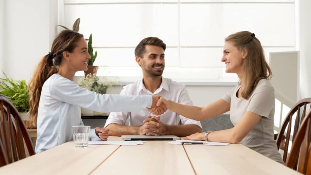 Klatsch und Tratsch am Arbeitsplatz: Zwei Frauen reichen sich die Hände, Mediator sitzt lächelnd dabei.